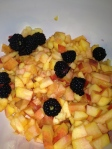 Next, chop up 2 peaches, mix with the melons and add the black berries.