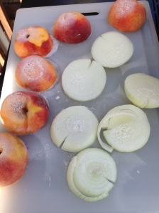 Sliced onions and peaches getting ready to grill.